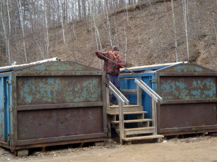 A transfer station attendant works to shift contents of the plastic/glass recycling bin as the container fills.