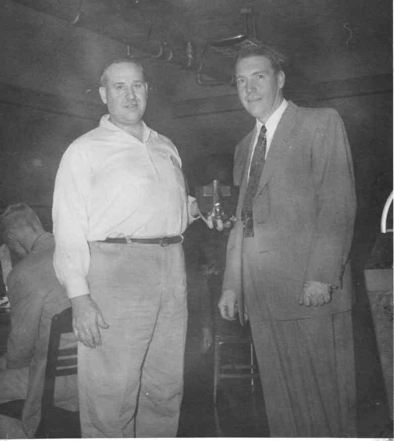 Ralph Oswald, right, receives an award for growing 100-bushel-per-acre corn in 1954.