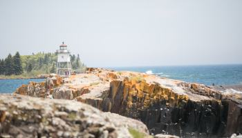 Photo of shoreline and lighthouse in Grand Marais