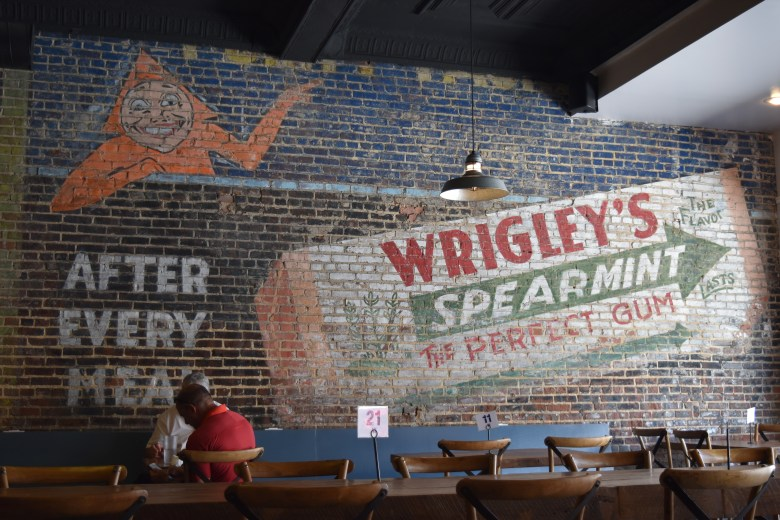 An old mural on the wall of the taproom advertises Wrigley's spearmint gum.