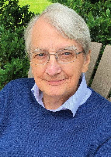 Gurney sits in a chair with green foliage behind him, wearing glasses, a light blue collared shirt and a darker blue sweater.