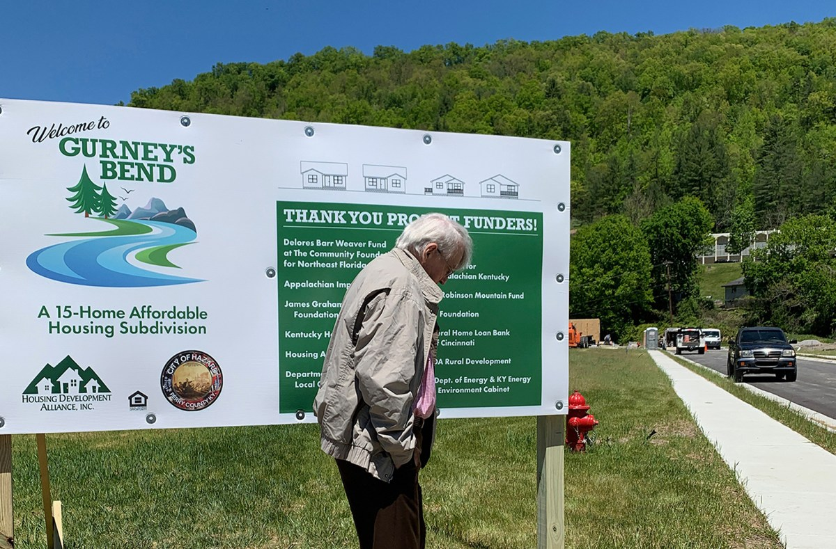 Gurney stands in front of a sign detailing the affordable housing subdivision, called Gurney's Bend.