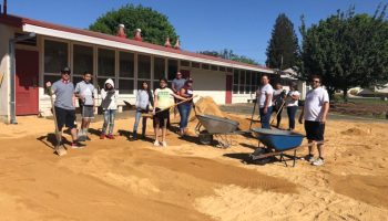 A group of students, shovels in hands, construct an outdoor learning space.
