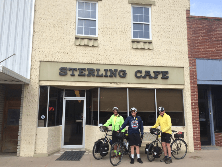 Photo of three bikers outside the entry of a restaurant labeled with Sterling Cafe sign.