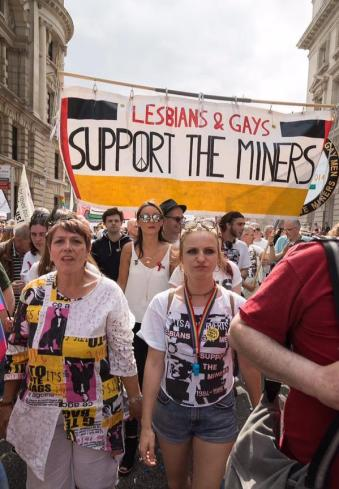 """Marchers carry a banner with the words """"Lesbians & Gays Support the Miners."""""""