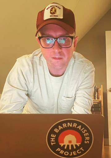 Garrett Bucks sits in front of his computer wearing glasses and a baseball cap,