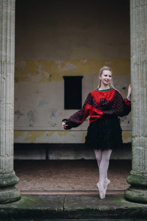 Front view of red upcycled acrylic jumper with tartan wool batwing with black tutu. Ballerina posing at Sydney gardens.