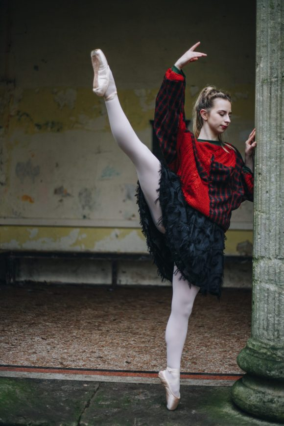 Ballerina Grace Richardson wearing an oversized ref tartan and upcycled wool batwing jumper. Posing on pointe doing the splits I'm a black textured tutu at the Holbourne museum.