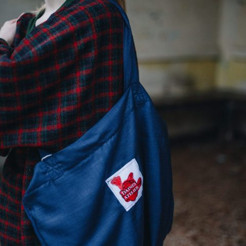 Detail shot of navy tote bag with Daines atelier logo with the oversized tartan jumper