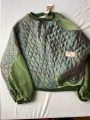 Front flat of green batwing jumper with velvet panels and quilted silk panels from a vintage jacket still featuring it's original labelling