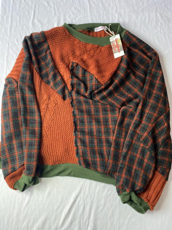 Front flat lay of batwing jumper made from upcycled acrylic jumper and vintage remnant tartan. Featuring lots of panels committing to being zero waste