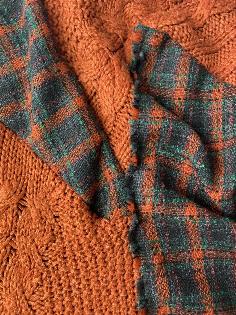 Material detail shot of orange acrylic jumper and tartan with raw selvedge edge committing to a zero waste design
