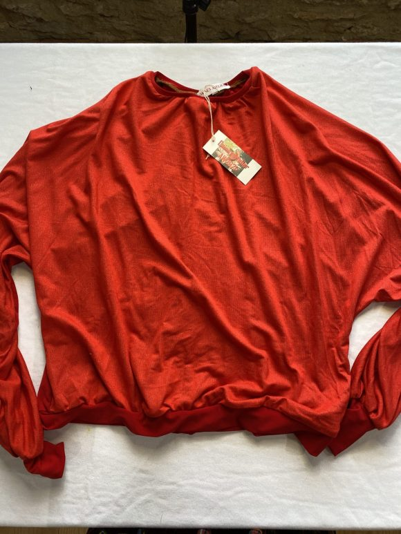 Flatlay image of front of red batting jumper in dead stock jersey