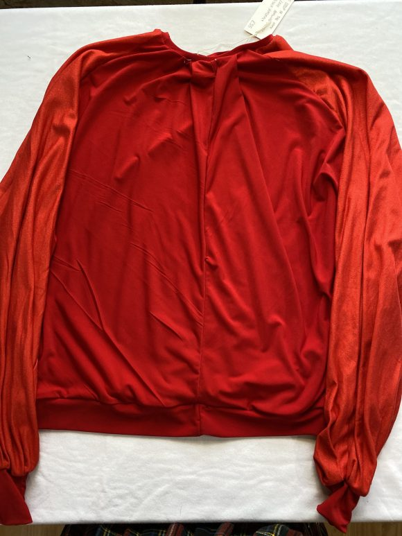 Flatlay image of red batting jumper with matching red cuffs showing the drape of the jersey