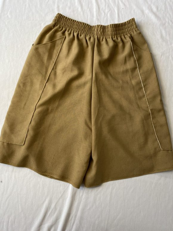 Flat lay of oversized long boxing shorts with elasticated waist and long pockets in beige vintage linen