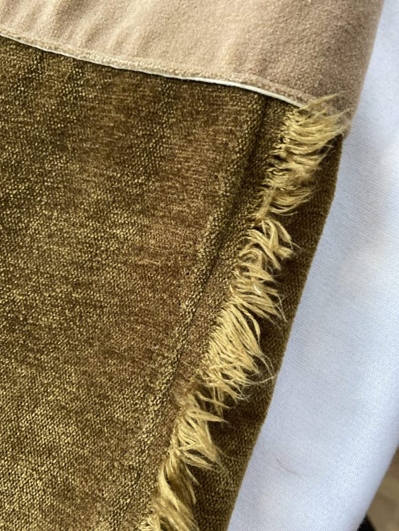 Detail shot of raw selvedge on brown corduroy trousers showing a frayed edge. Zero waste and sustainable design
