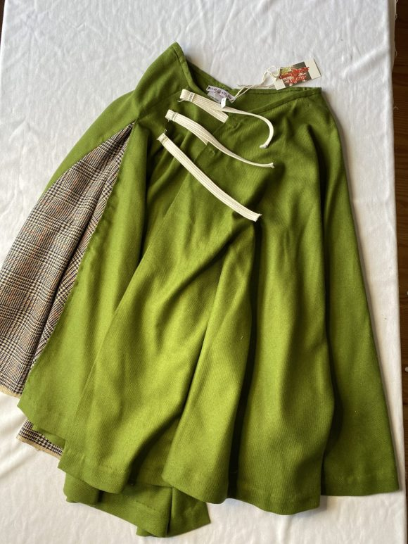 Front flatlay of wool circular skirt grey tartan and green wool circle skirt with irregular hem