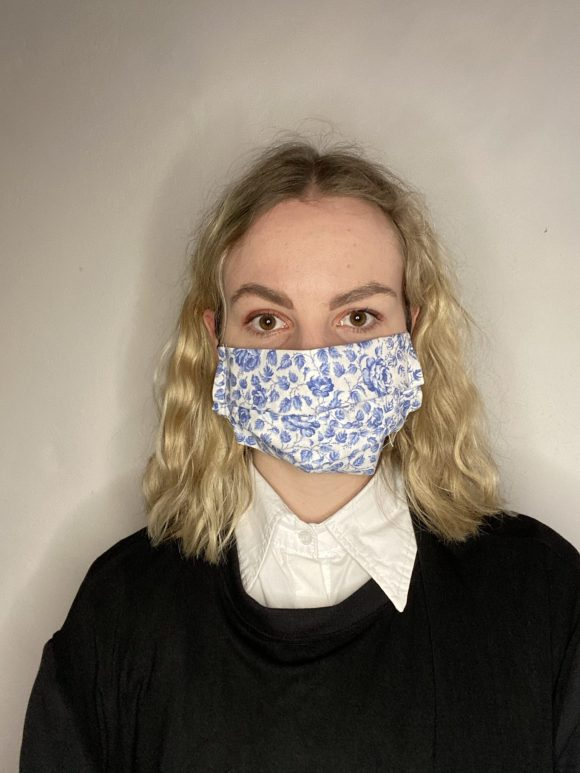 Handmade breathable facemask with filter pocket and adjustable elastic made from vintage remnant materials. On Evie with curly hair in blue floral