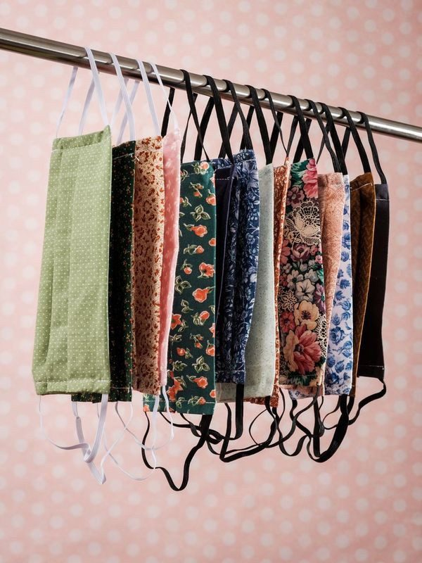 Photograph by Yousef Al Nasser Facemasks hanging on a clothing rail with elastics. They are a variety of different vintage floral patterns.