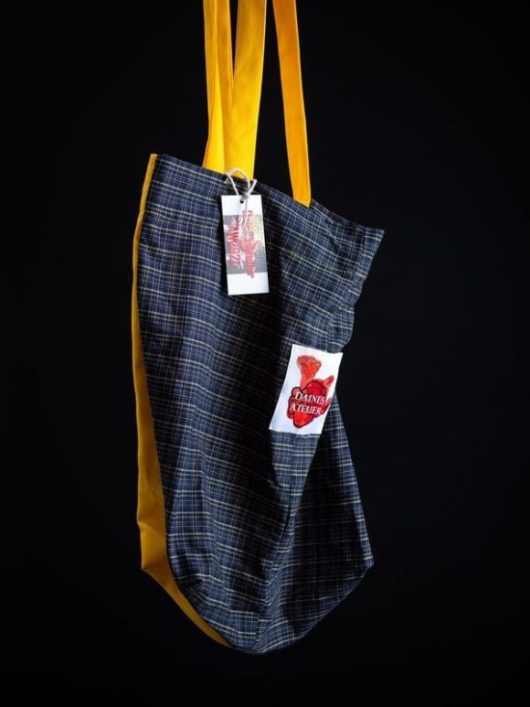 Floating image of tote bag in tartan and yellow with Daines atelier logo branding