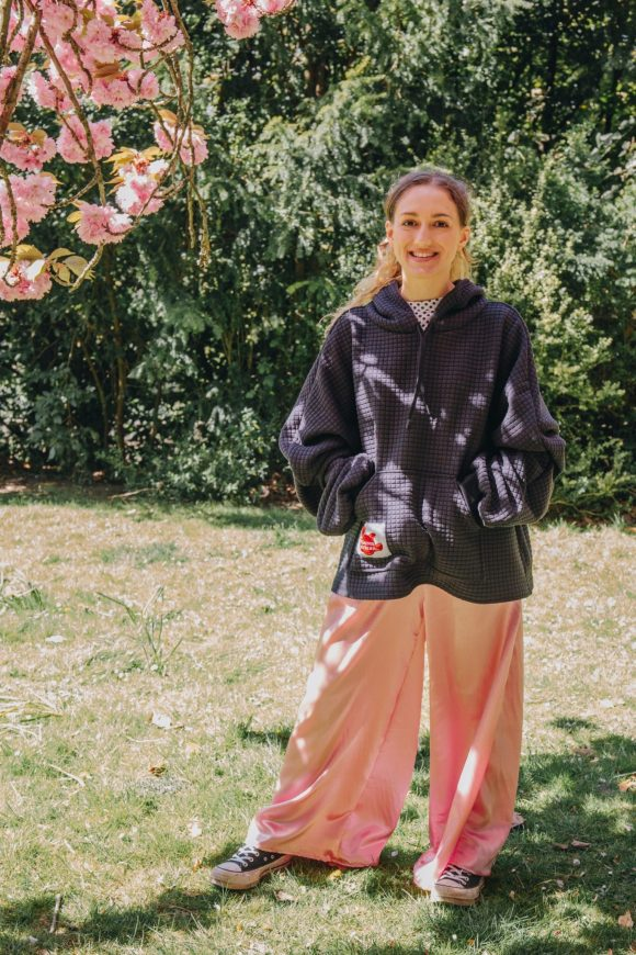 Made to order wide leg mimosa trousers with elasticated waistband and black quikted hoodie all made from dead stock materials from Amorthreads. Martha Rice is photographed by Maisie Lee Walker in Sydney Gardens Bath