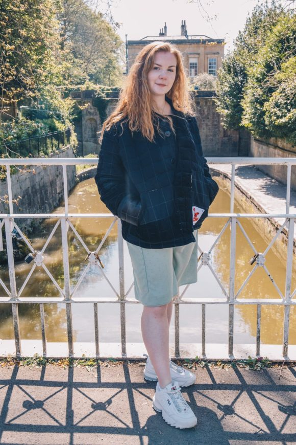 Grace Daines wears the black quilted jacket made from vintage corduroy and polyester lining. This one of a kin upcycled product is photographed by Maisie Lee Walker in Bath