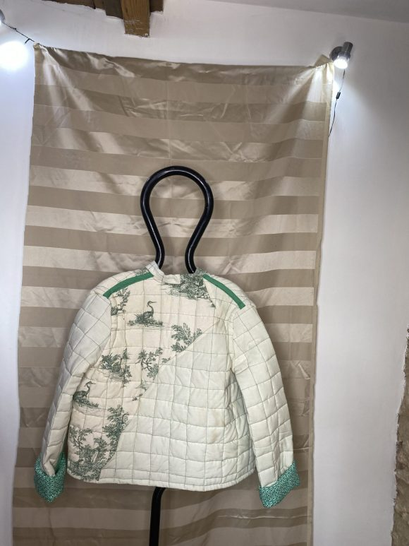 Back photo of green quilted Jacket. Featuring irregular panelling and bias tape. Upcycled clothing.