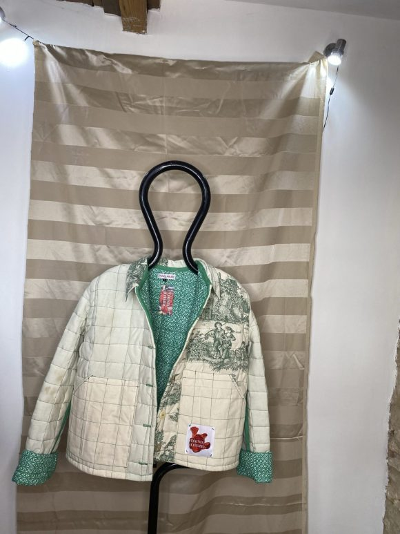 Front photo of Green Quilted Jacket taken in Frome Studio at Silk Mill. Buttons long sleeve, unisex quilted jacket.