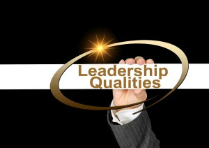 a hand holding a banner that says Leadership Qualities with a gold circle arounnd it and on a black background