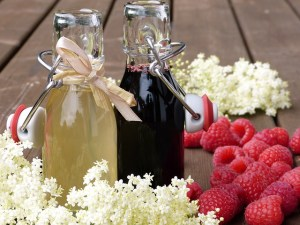 Two jars or syrup with ribbons tied around the lid. One is basic syrup, one is raspberry syrup