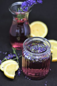 Lavender and thyme simple syrup in a glass jar with lemons around the glass.