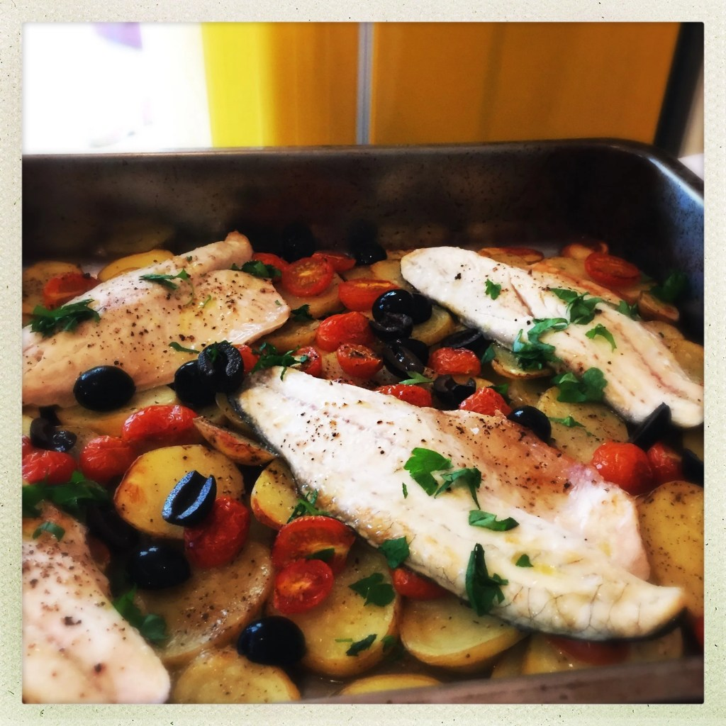 roasting tin layered up with roasted sliced new potatoes, baby plum tomatoes and big black olives, 4 sea bass fillets laid on top scattered with chopped flat leaf parsley and drizzled with olive oil and lemon juice.