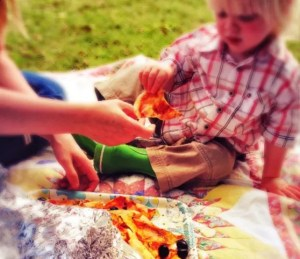 toddler eating pizza on a picnic