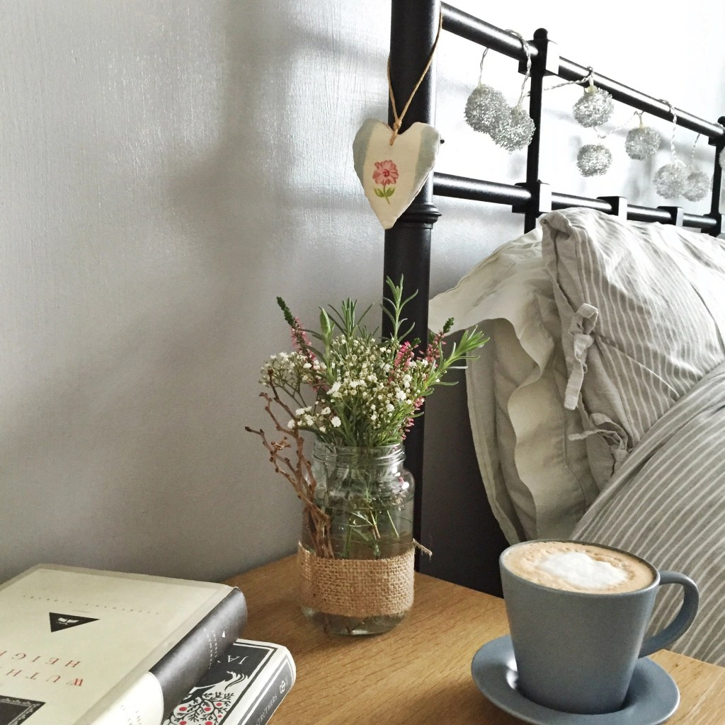 black iron bedstead with silver ball fairy lights entwined around head, grey and white striped bedding. Wooden bedside table holding jam jar with garden flowers and herbs, cup of coffee in blue Ikea cup and two books Withering Heights and Red Sky at Night