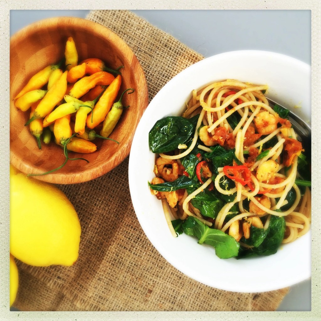 hessian clothe with dish of wholewheat spaghetti with prawns, chilli, sun dried tomatoes and spinach, wooden bowl of orange coloured chillies and two lemons by the side of it
