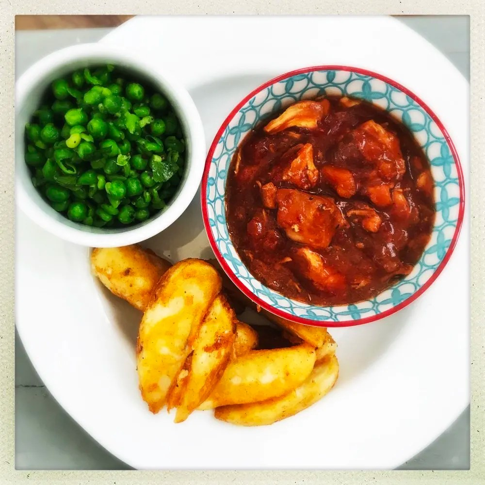 slow cooker peri peri chicken stew served with oven baked potato wedges and homemade Nando style peas