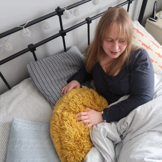 woman lying in IKEA iron bedstead, crisp grey and white striped bedding, fluffy mustard cushion and blue and white woollen cushion.