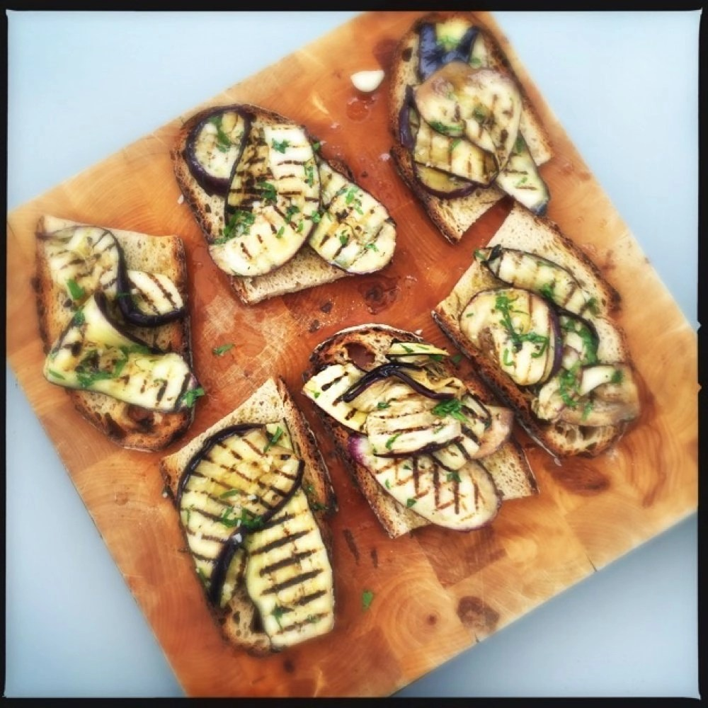 wooden board with six bruschetta topped with grilled aubergines