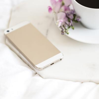 Gold iPhone sitting on table next to cup of coffee with flowers