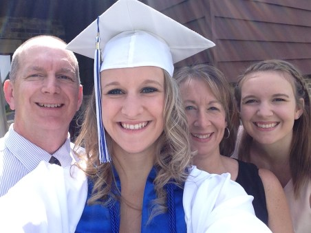 My Niece, Kaitlin In Her Graduation Cap And Gown And Behind Kaitlin From Left To Right Is Her Dad, Her Mom And Her Older Sister