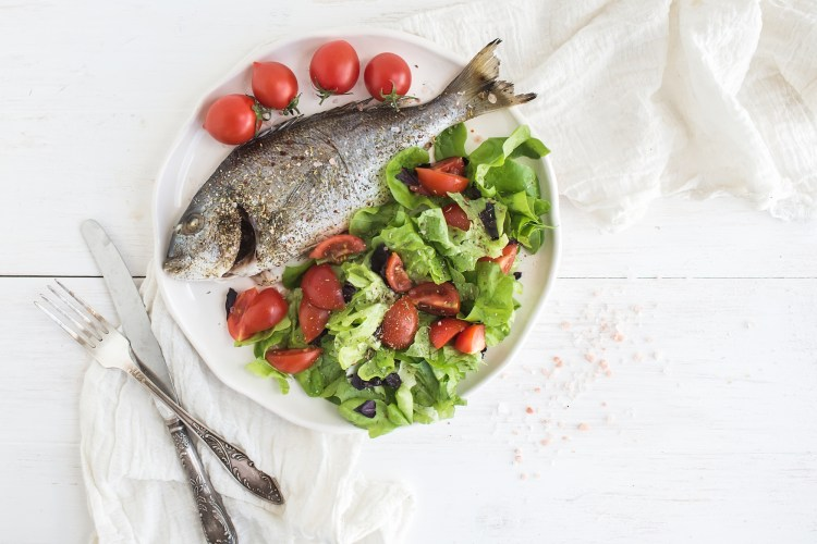 Cooked sea bream fish with fresh vegetable salad on ceramic plate over white rustic wooden backdrop, top view, copy space