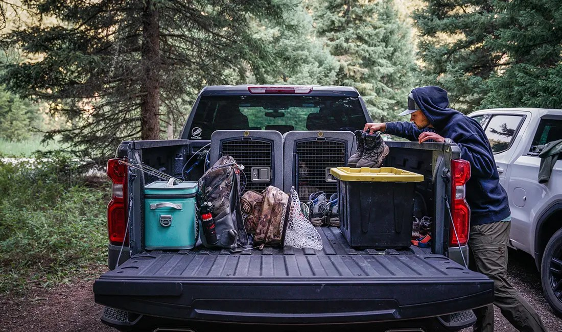 A man pulls stuff out of the bed of a truck.