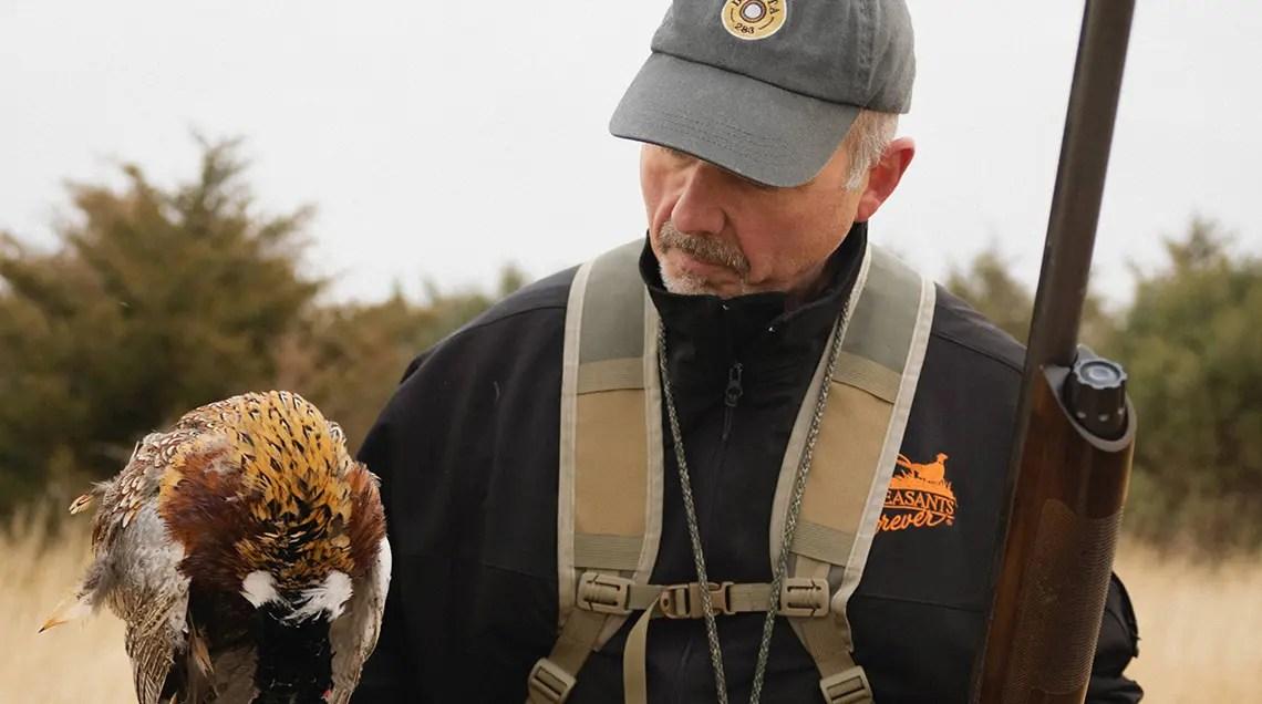 Greg Cronkhite holds a dead pheasant.