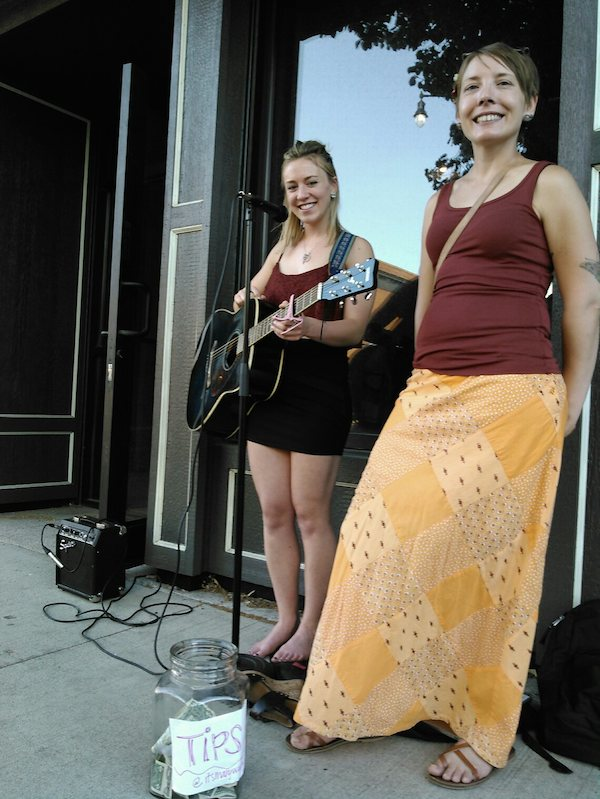 Singer-songwriter Mary Elizabeth Wachs (left), her tip jar, and her loyal friend, who really doesn't want you to know what she has in her left hand.