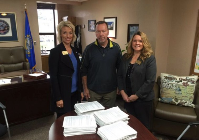 Steven C. Hildebrand (center) delivers a petition with 20,081 signatures to Secretary of State Shantel Krebs (left) and Deputy SOS Kea Warne (right) to place a 36% rate cap on payday and car title loans on South Dakota's 2016 ballot. Photo from Secretary of State's office, 2015.11.05.