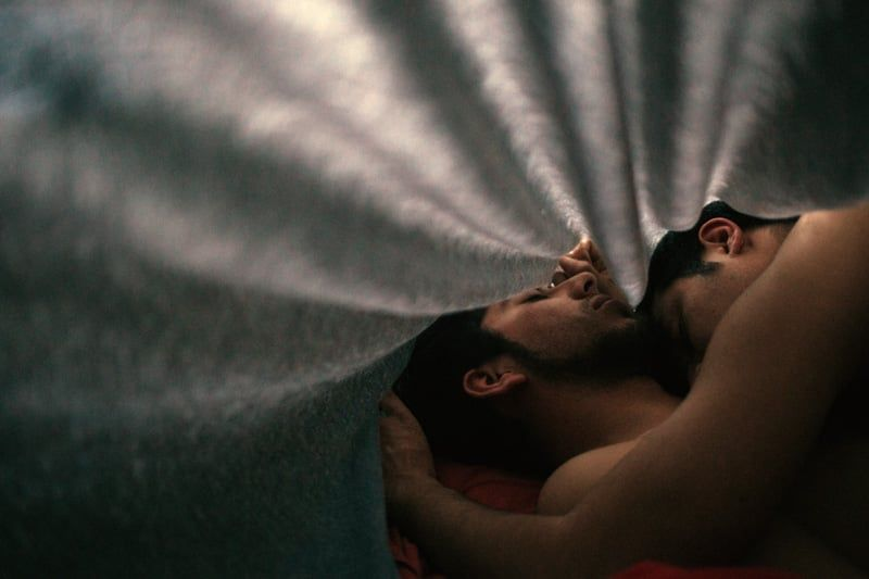 Two men embracing in bed.