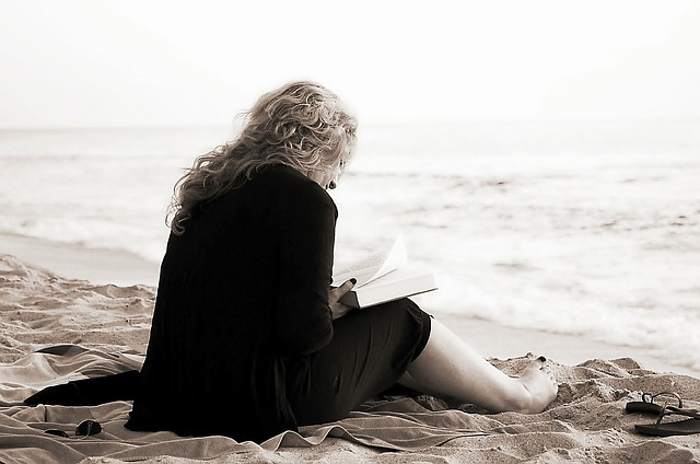 woman-reading-hardback-book-on-beach