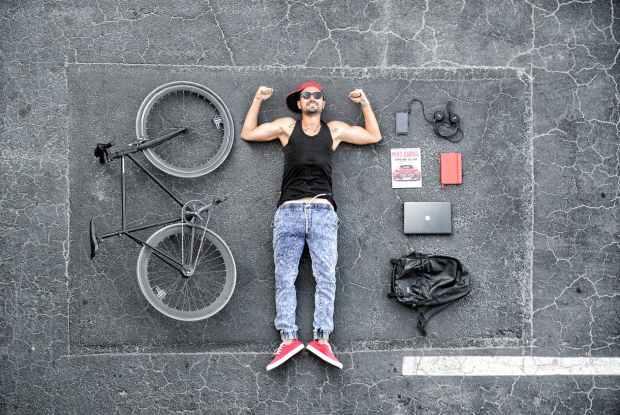 man in black tank top laying on gray concrete surface near black bike