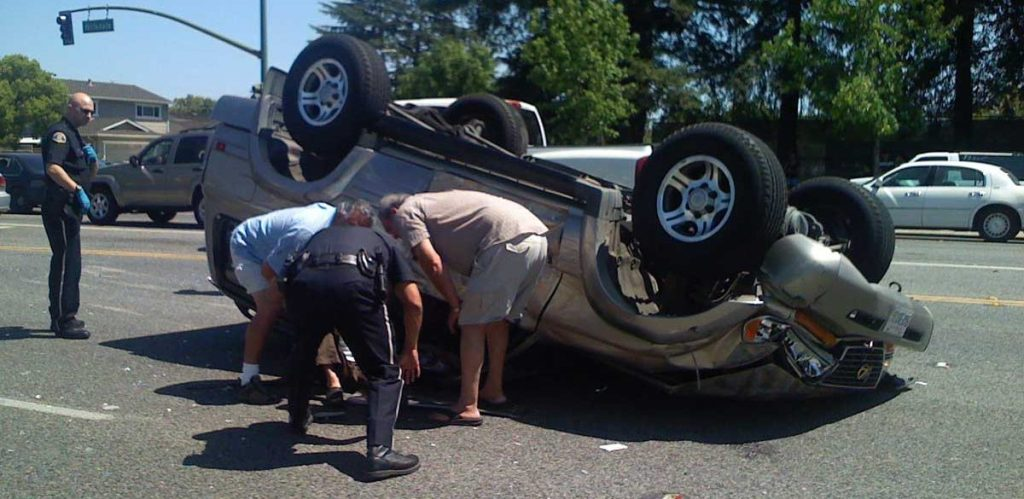 Car upside down with people helping, Causes of auto accidents in Dallas