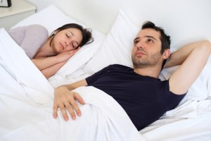 man concerned in bed with female partner